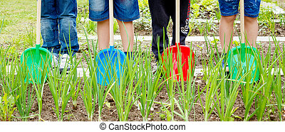 Four boys playing with plastic shovels in the garden
