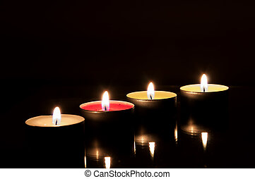 Four burning candles in the dark