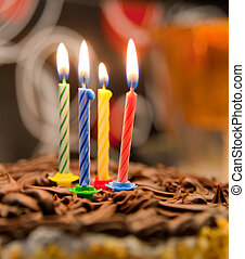 four burning candles on a birthday cake