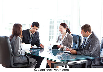 Four business people during a meeting sitting around a table...