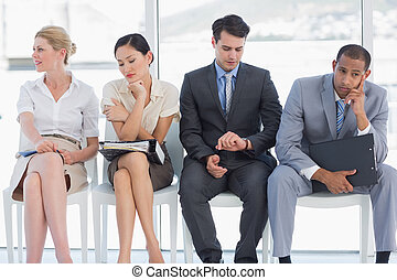 Four business people waiting for job interview in a bright...