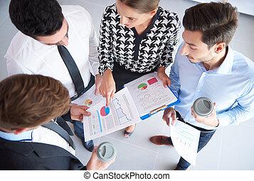 Four businessmen analyzing some documents