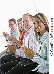 Four businesspeople applauding indoors smiling