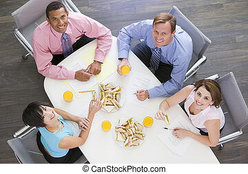 Four businesspeople at boardroom table with sandwiches smiling