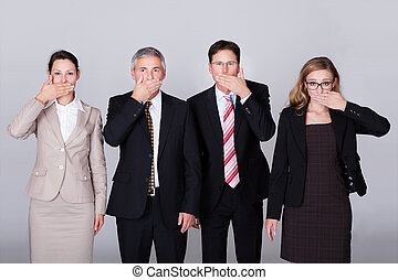 Four businesspeople gesturing for silence