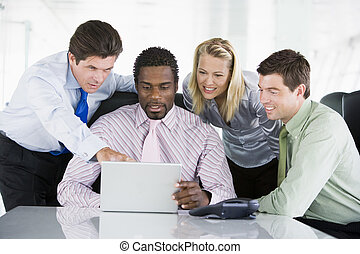 Four businesspeople in a boardroom pointing at laptop and smilin