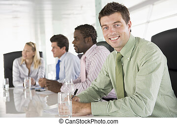 Four businesspeople in a boardroom smiling