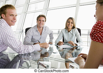 Four businesspeople in a boardroom with paperwork smiling