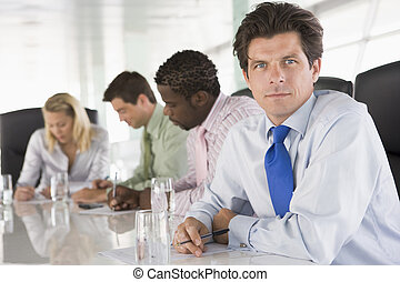 Four businesspeople in a boardroom writing