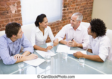 Four businesspeople in boardroom smiling