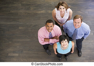 Four businesspeople standing indoors smiling