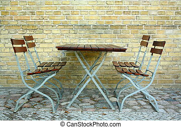Four chairs and table in beer garden on brick wall