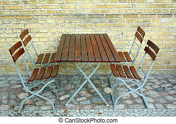 Four chairs and table in beer garden on brick wall, top view