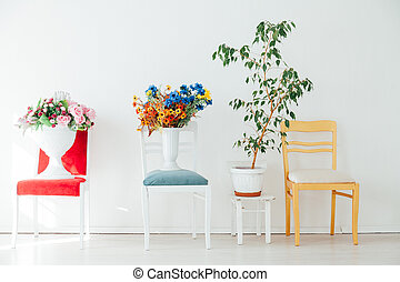 four chairs with flowers in the interior of a white empty room