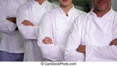 Four cheerful chefs looking at camera with arms crossed in a...