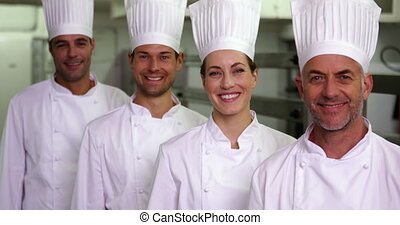 Four cheerful chefs looking at camera making ok sign in a...