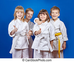 Four cheerful sportsman in karategi are showing finger super