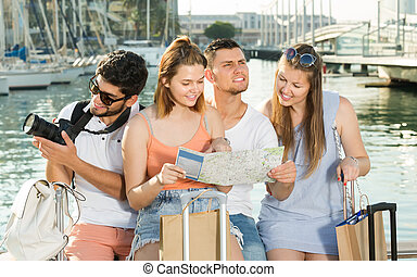 Four cheerful traveling young people searching for direction using paper map on waterfront in town