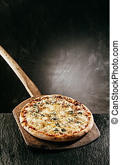 Four Cheese Italian Pizza on a restaurant menu with a flame grilled steaming hot pizza served on a wooden board in front of a blank chalkboard with copyspace for a menu or recipe