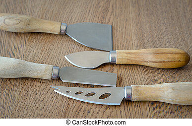 Four cheese knives on wooden background
