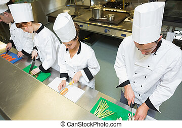 Four chefs preparing food at counter