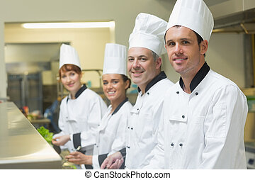Four chefs working in a kitchen standing in a row