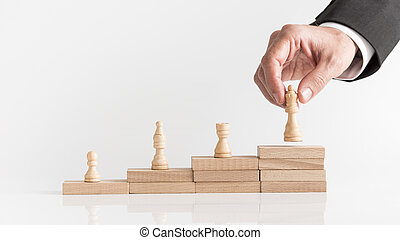 Four chess pieces on a stepped stack of blocks