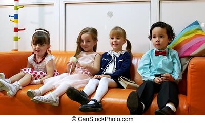 Four children sit in baby barbershop. Smiling