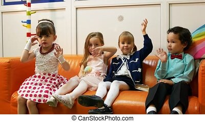 Four children sit on sofa in baby barbershop. Smiling