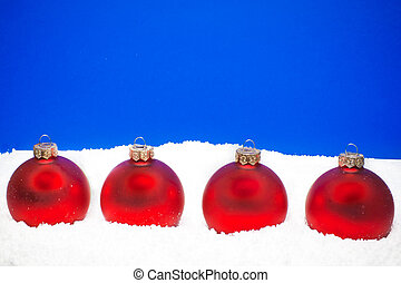four christmas balls on the snow