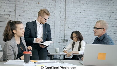 Four collar workers making notes in agenda and talking -...