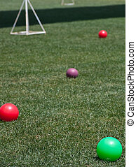 Four Colored Bocce Balls on Green Lawn