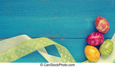 Four colorful Easter eggs on blue wood