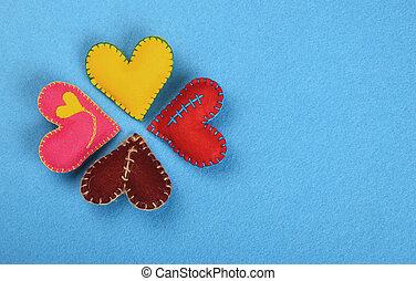 Four colorful felt craft art hearts on blue