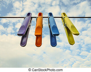 four colorful plastic clothespins hanging from a rope