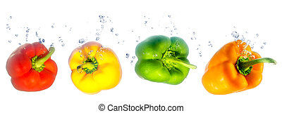four coloured paprikas falling in the water