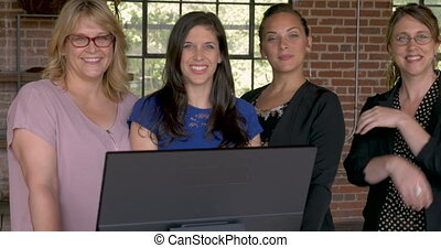 Four confident successful business women smiling behind...