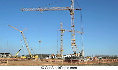 Four construction cranes working on the site