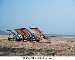Four deck chairs on beach - Four deck chairs on sandy beach...