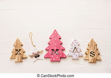 Four decorative wooden Christmas trees with carved letters xmas.