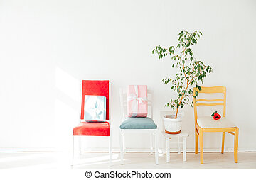 four different chairs in the interior of the white room