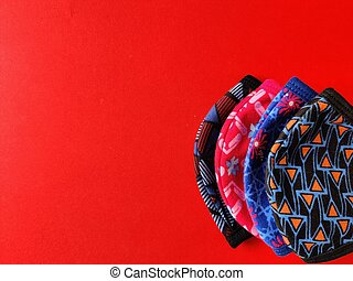 Four different colored printed face masks isolated on red background. Copy space. Corona virus protection