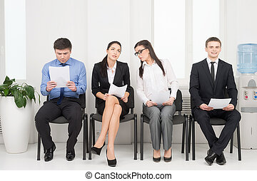Four different people waiting for interview. Looking nervous...