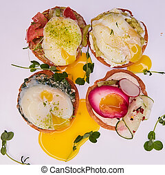 Four different toasts with poached egg.