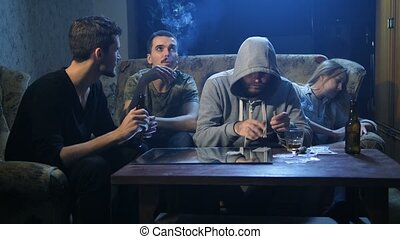 Four drug addicts using cocaine indoors at night - Young...