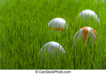 Four easter eggs on green young grass