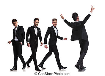 four elegant men in tuxedoes walking in different directions