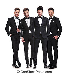 four elegant young men in tuxedos standing together