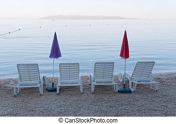 Four empty deck chair and parasol