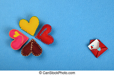 Four felt craft art hearts and letter on blue